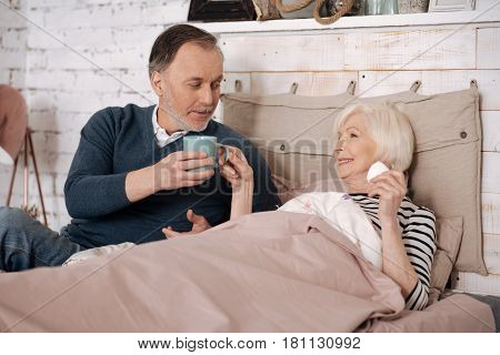 You need it. Old handsome man is giving hot drink to his elderly ill wife lying on bed covered with warm blanket.