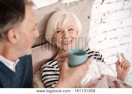 My darling. Smiling senior woman is going to take some hot drink from her loving husband.