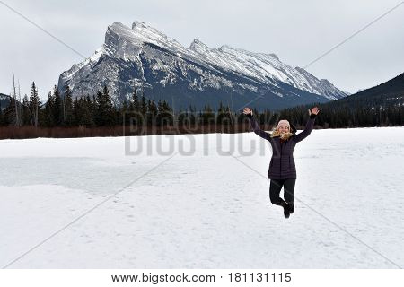 Picture of a woman jumping in the air on frozen lake with Mount Rundle in background in Banff National Park,Alberta,Canada.