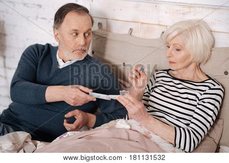 For better. Close up of aged sick lady taking pill from her elderly husband.