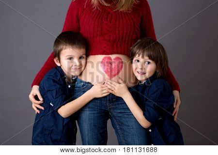 Beautiful Preschool Children, Hugging Their Pregnant Mom