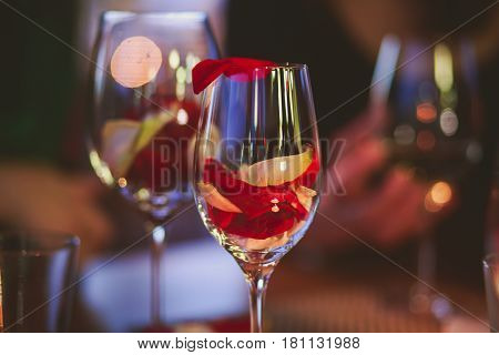 Beautiful glass with rose leafs, rose-petal, rose petals on a romantic date with wine, candles in candlelight and with celebrating couple on the background, interior for a romantic date diner