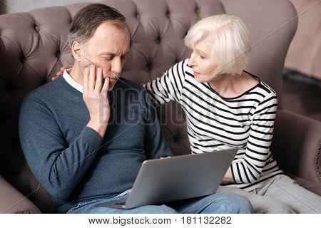 Take a pill. Pretty aged woman is giving support to her husband having strong toothache while using laptop.