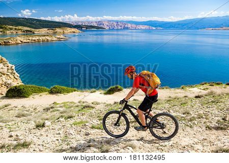 Mountain biker riding on bike in summer inspirational mountains and sea landscape view. Man cycling MTB on enduro dirt and rocky trail track. Sport fitness motivation and inspiration outdoors.