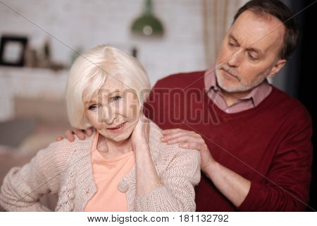 Oh no again. Elderly man standing behind his wife suffering from strong neck ache.