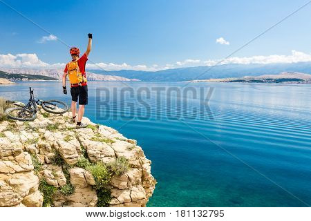 Mountain biker success celebrating concept looking at view and traveling on bike summer sea landscape. Happy male rider cycling MTB bicycle. Fitness motivation and inspiration in beautiful nature.