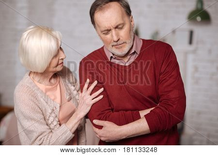 Is it appendix. Portrait of elderly man standing and touching his aching stomach area while his loving wife giving support to him.
