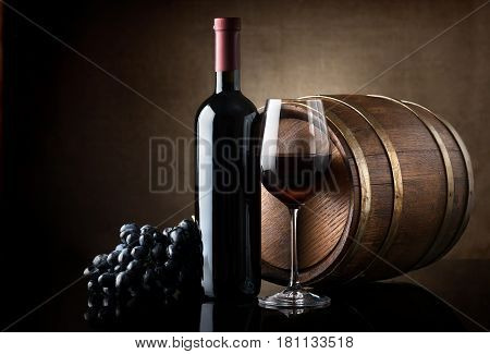 Bottle of red wine, grapes and wooden barrel