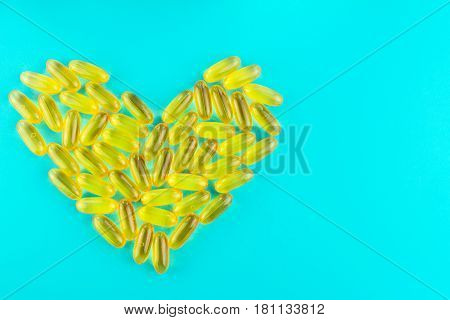 Lot of yellow capsules omega 3 fatty acid fish oil in heart shape on blue background