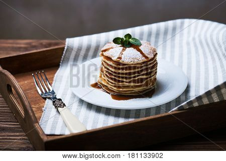 American pancakes on a plate with mint and caramel syrop. Dark background. Setted on a wooden tray with a fork