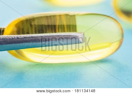 Tweezers keeps one yellow capsule of omega 3 fatty acid fish oil on blue background macro image