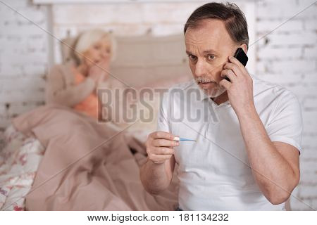 Come soon. Worried elderly man holding thermometer and calling emergency on background of his sick senior wife.