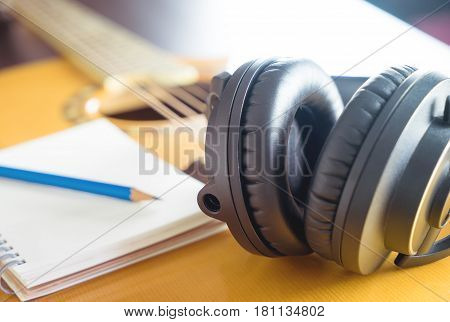 Songwriter equipments with headphone and notebook on guitar
