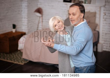 Expressing happiness. Smiling elderly lady dancing with her loving husband at home.