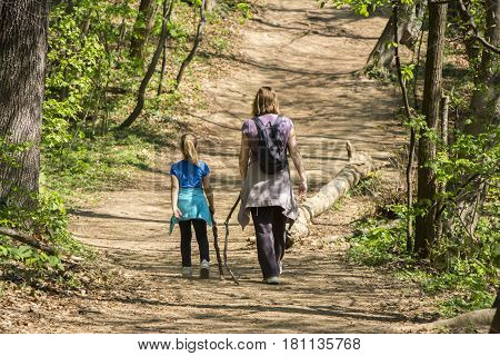 Mother and daughter walking in spring forest