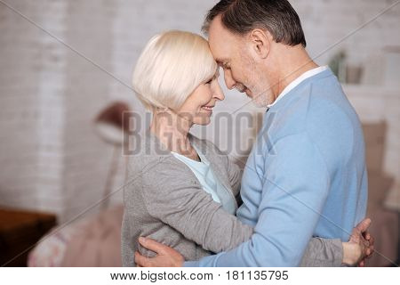 My sweetheart. Portrait of aged couple embracing and looking at each other while standing closely at home.
