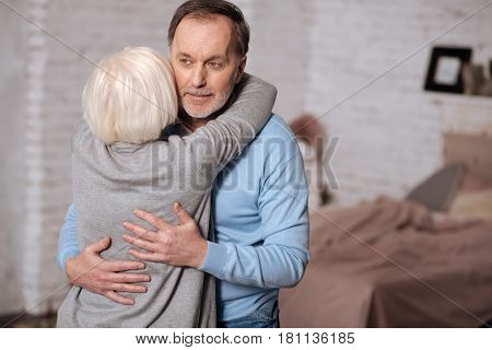 My everything. Back view of aged lady embracing her lovely husband while standing at home.