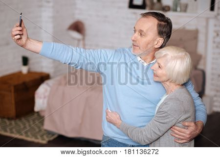 We are modern. Portrait of handsome elderly man embracing his wife and taking selfie while standing at home.