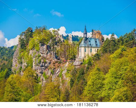Ruins of Vranov Castle with small rock chapel, Pantheon, in Mala Skala on sunny summer day with blue sky and lush green trees, Bohemian Paradise, aka Cesky Raj, Czech Republic, Europe.