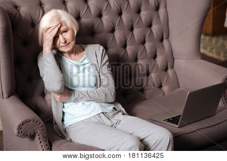 I feel bad. Portrait of sad aged lady sitting on couch and touching her forehead.