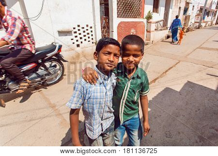 BADAMI, INDIA - FEB 8, 2017: Unidentified boys meet on the narrow street of indian town with transport traffic at hot day in Karnataka state on February 8, 2017. Population of Karnataka is 62000000 people