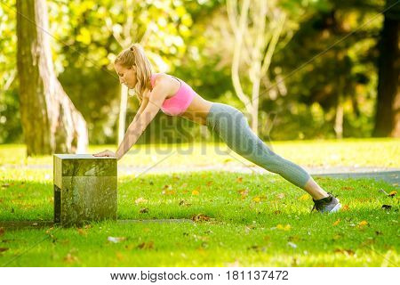 young happy smiling caucasian woman doing exercises in the park, outdoor fitness