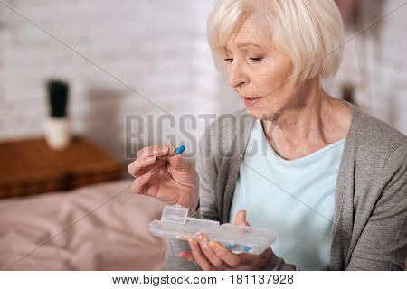 My small help. Close up side view of senior lady holding pill and intently looking at it.