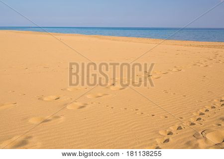 Footprints in the sand at sunset. Beautiful sandy tropical beach with sea waves. Footsteps on the shore