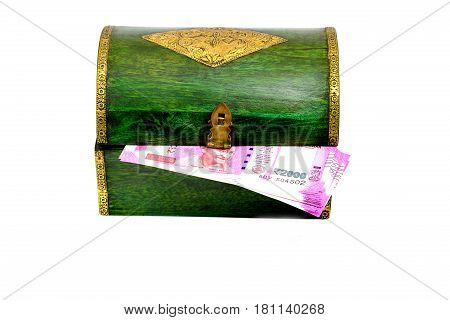 Vintage wooden green casket from India with new indian rupees notes isolated on white