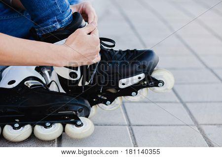 Closeup of man guy putting on roller skates