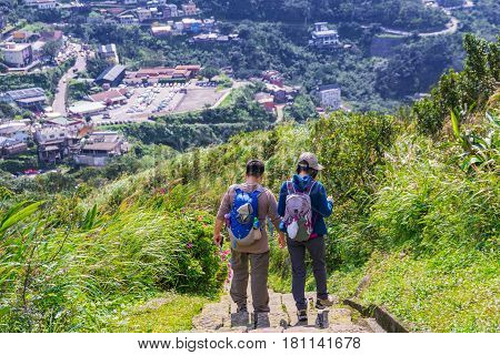 TAIPEI TAIWAN - MARCH 12: This is a view of a couple walking down Jilong mountain path on a sunny day in Jiufen town on March 12 2017 in Taipei