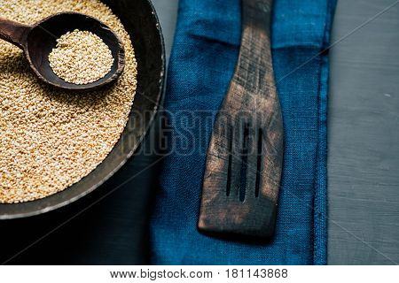 A spoon of seed seeds in a natural wooden spoon in a vintage pan in rustic style against a background of a dark-colored natural textured wood