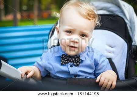 Baby blond boy with blue shirt and black bow tie sitting in modern stroller on walk in park. Child in buggy Little kid in pushchair. Transportation for family with infant