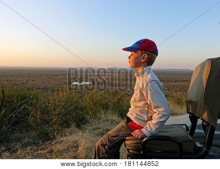 Picture of a boy sitting on the tracker`s seat of a safari vehicle,enjoying the view, South Africa.