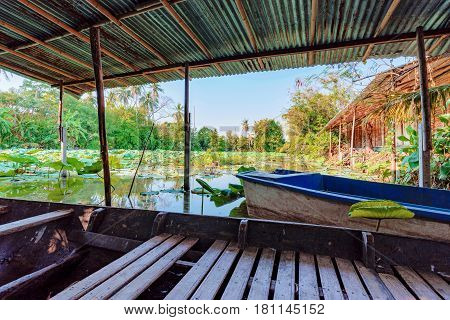 Rural jungle hut by a canal with a boat in Thailand