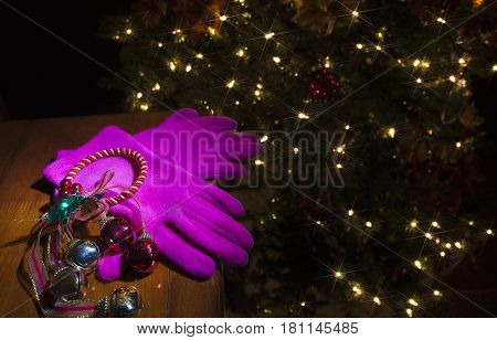 Pink gloves on a table with a Christmas tree with lights behind