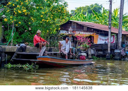 BANGKOK THAILAND - FEBRUARY 05: Thai people relaxing and talking outside a riverside house in a rural area of Bangkok February 05 2017 in Bangkok