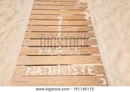 Wooden Path To Access The Beach On Which Is Written Nudist Beach