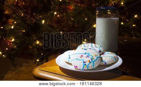 Cookies with white frosting and milk next to the Christmas tree