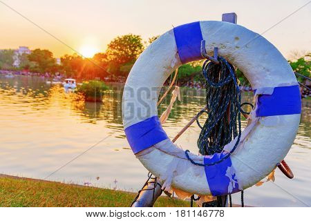 Life buoy with out of focus lake and sunset in the background in Chatuchak park