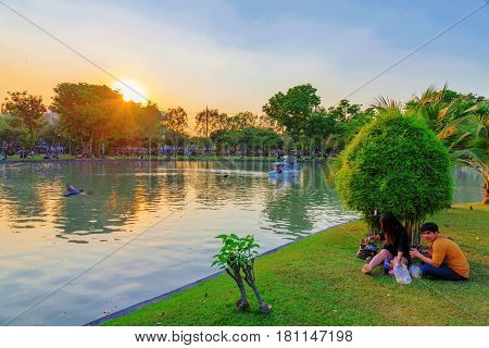 BANGKOK THAILAND - FEBRUARY 04: Romantic scene of a Thai couple sitting by the lake in Chatuchak park during sunset on February 04 2017 in Bangkok