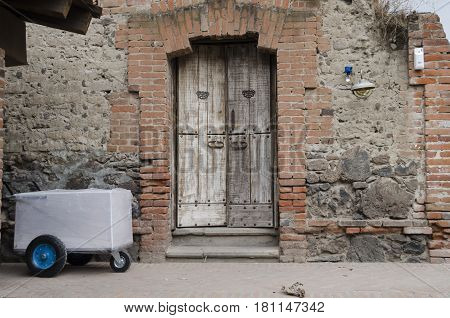 VAL'QUIRICO, TLAXCALA, MEXICO- MARCH 25, 2017: Facade with a stone wall with bricks and an ancient door in Val'Quirico, Tlaxcala, Mexico