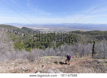 A Bearded Middle Aged Man Hiking in the Mountains Above a City