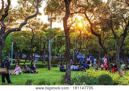 BANGKOK THAILAND - FEBRUARY 04: Chatuchak park trees and nature area with people sitting and relaxing on the grass during sunset on February 04 2017 in Bangkok