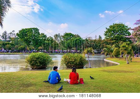 BANGKOK THAILAND - FEBRUARY 04: Couple sitting by the lake in Chatuchak park a famous park in Bangkok on February 04 2017 in Bangkok
