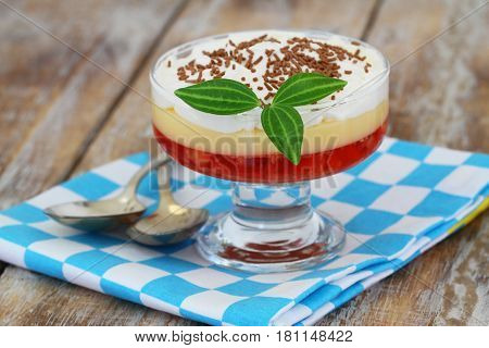 Trifle in dessert glass on checkered cloth on rustic wooden surface