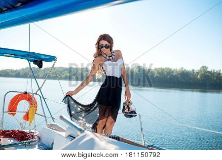 Young sexy woman on her private yacht