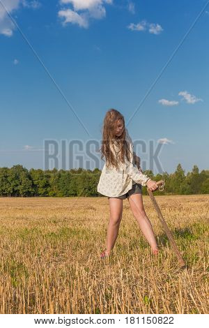 Teengirl with a scythe at summer field traditional countrywoman