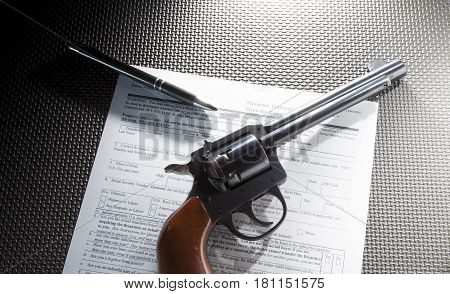 Revolver and pen on top of the paperwork to purchase the handgun