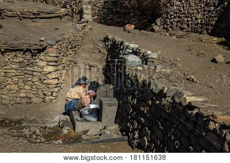CHHYONGGUR, NEPAL - NOVEMBER 21, 2016: Nepalese woman is washing clothes in Chongur village, Mustang Nepal.